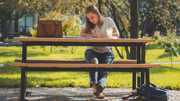 Student working outside planning how much college will cost